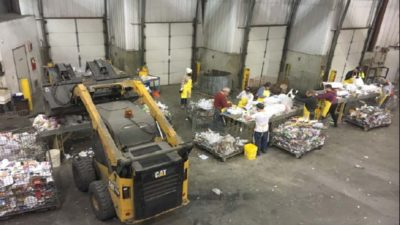 People inside the recycling facility sorting garbage into different bins while a skidsteer scoops more material